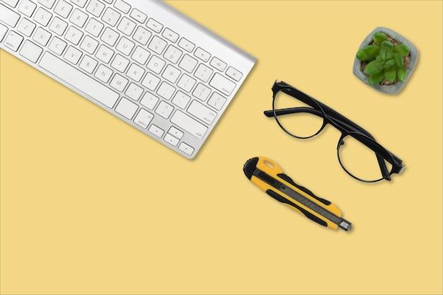 Очки, резак, растение в горшке и белая клавиатура на желтом фоне