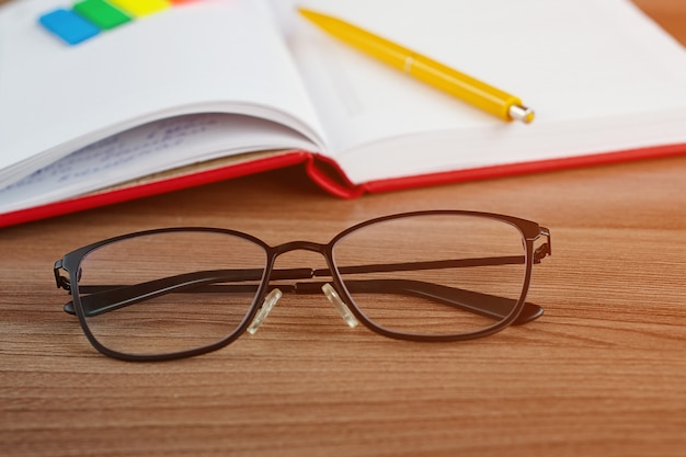 Glasses on the desktop with a notebook in the background