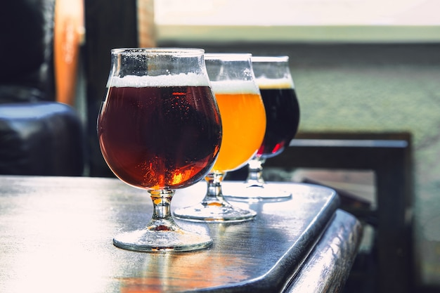 Glasses of different kinds of dark and light beer on wooden table in line.