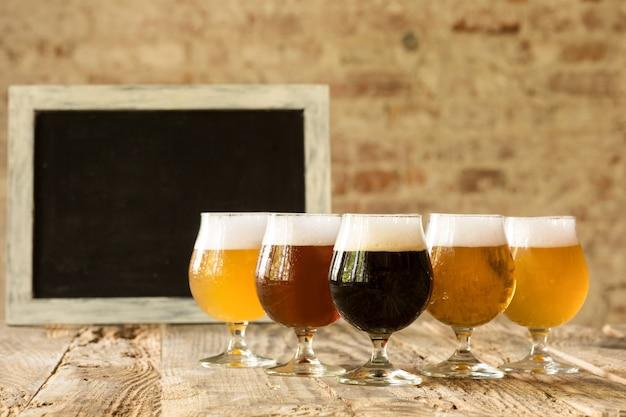 Bicchieri di diversi tipi di birra scura e leggera sul tavolo di legno in linea