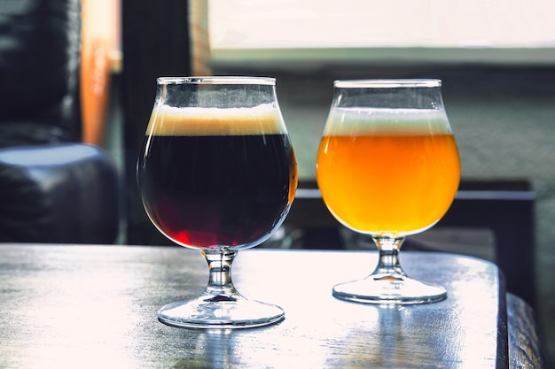 Glasses of different kinds of dark and light beer on wooden table in line