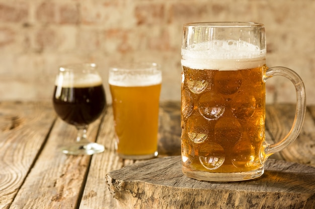Glasses of different kinds of dark and light beer on wooden table