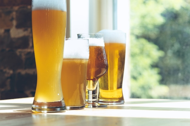 Glasses of different kinds of light beer in sunlight.