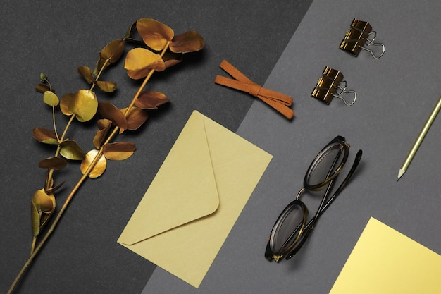 Glasses, envelope and gold branch on dark background