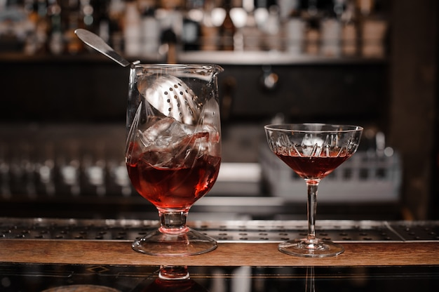 Glasses filled with red alcoholic drink arranged on the bar counter