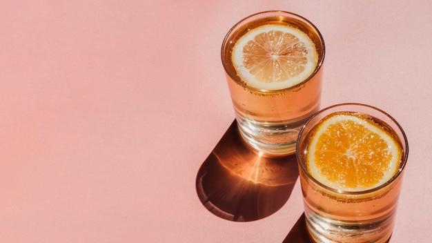 水とオレンジのスライスとコピースペースで満たされたメガネ