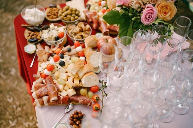 Бокалы для шампанского на столе с деликатесами и букетом роз