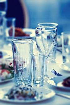 お祝いのテーブルで飲み物やカクテルのためのグラス