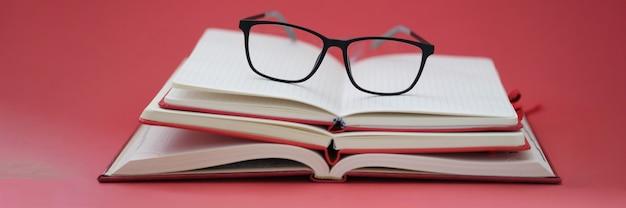 赤い背景のクローズアップのノートブックの山の上に横たわっている視力のためのメガネ
