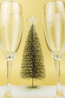 スパークリングワイン、クリスマスツリー、偽の雪、ゴールドの背景のメガネ。高品質の写真