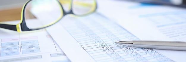 会計士の概念の数字のクローズアップ作業でドキュメントに横たわっているビジョンのためのメガネ