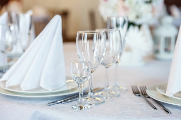 Glasses, fork, knife, napkin folded in pyramid, served for dinner in restaurant