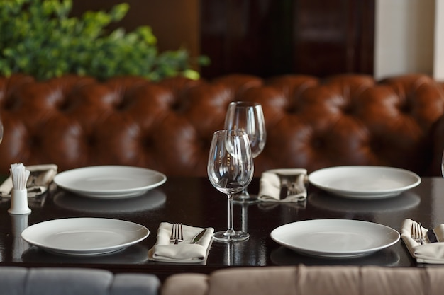 아늑한 인테리어의 고급 레스토랑에서 저녁 식사로 안경, 포크, 나이프를 제공합니다.