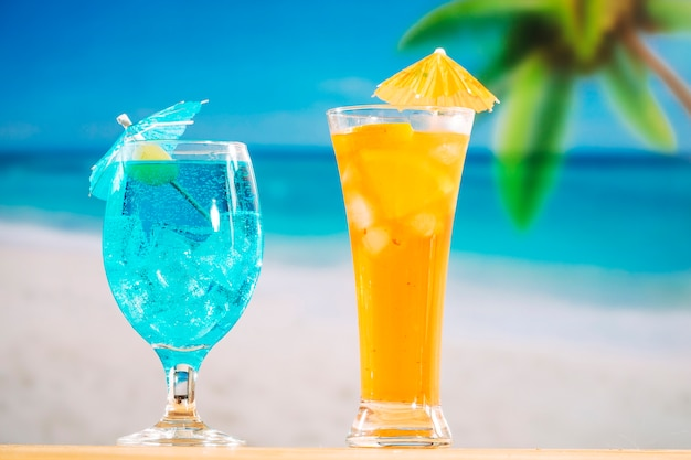 Glasses of fresh blue orange drink decorated with olive and umbrella