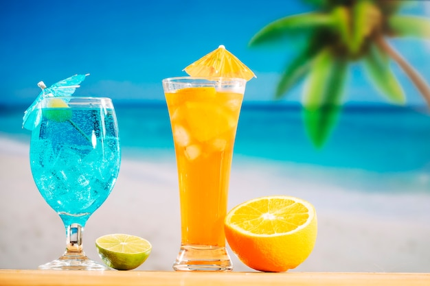 Glasses of fresh drinks decorated with olive umbrella and sliced lime orange