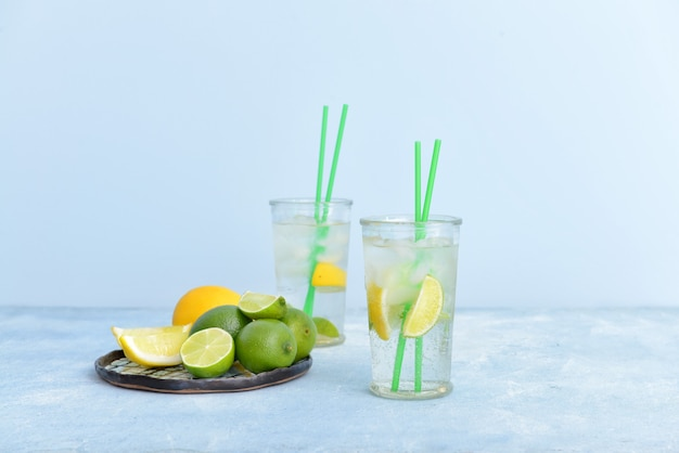 Glasses of fresh infused water with citrus fruits on table