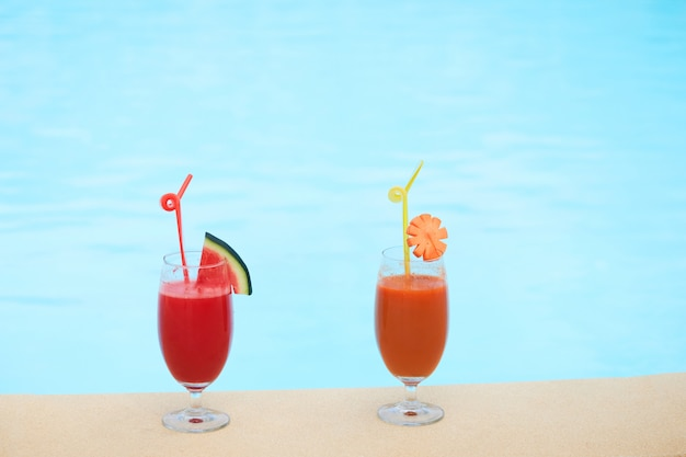 Glasses of fresh juice sitting on edge on swimming pool