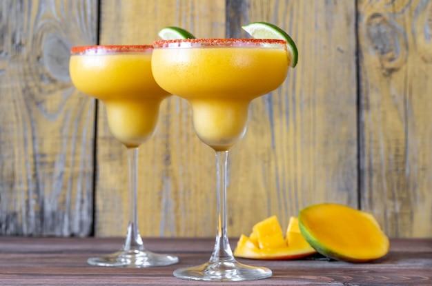 Glasses of frozen mango margarita cocktails garnished with paprika salt rim