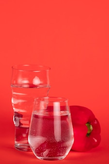Glasses full of water with red pepper