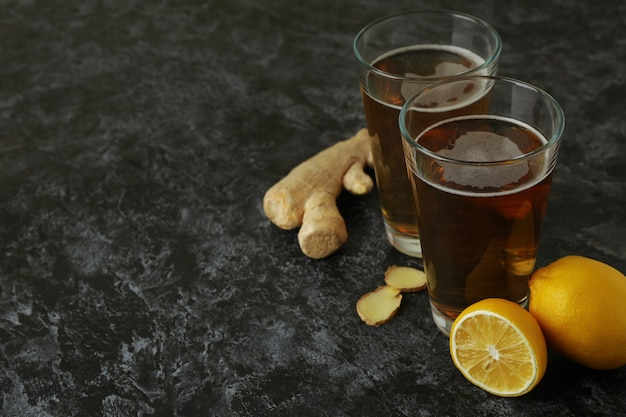 Glasses of ginger beer and ingredients on black smoky background