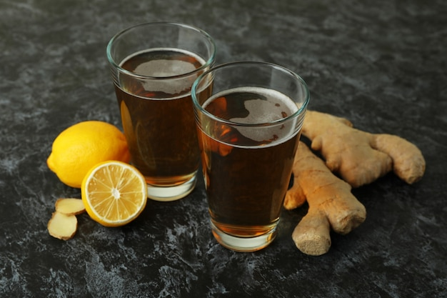 Glasses of ginger beer and ingredients on black smoky