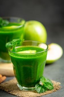 Bicchieri di frullato sano mela verde messi accanto a mele verdi fresche
