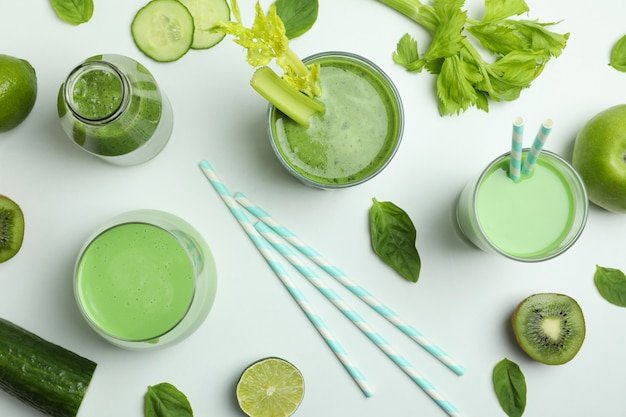 Glasses of green smoothie and ingredients on white background, top view