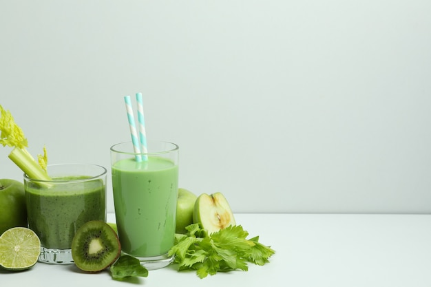 Glasses of green smoothie and ingredients on white table