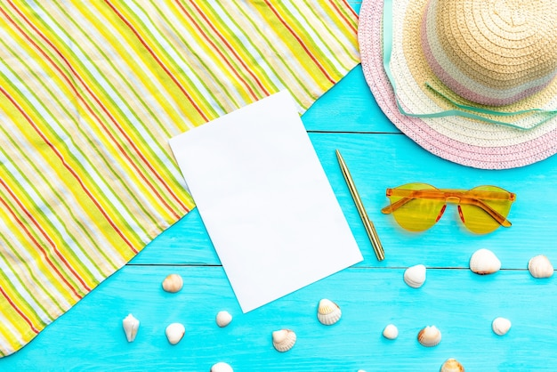 Glasses and hat for summer holidays on a blue background. notepad and ballpoint pens surrounded by shells and summer accessories. top view. copy space.