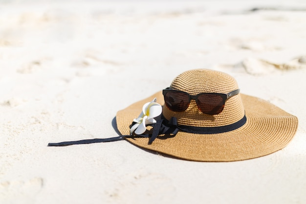 Glasses and a hat with frangipani flower on the beach.
