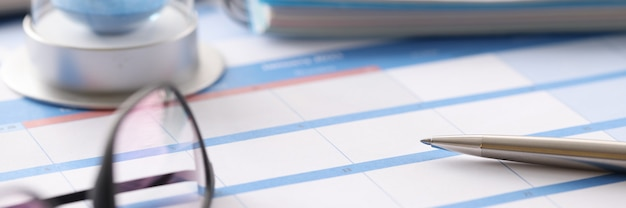 Glasses and hourglass are on calendar in office closeup. be in time by deadline concept