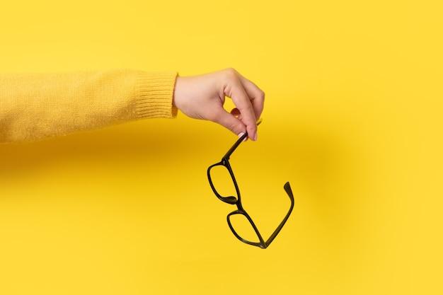노란색에 손에 안경 프리미엄 사진