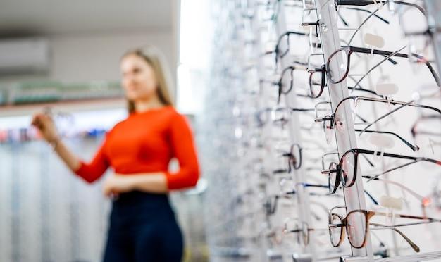 상점 진열대에 있는 안경. 안경점에서 안경을 쓰고 서십시오. 소녀, 배경 흐리게에 클라이언트입니다.