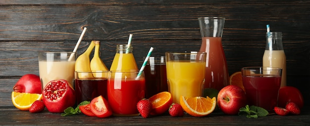 Glasses and jars with different juices on wooden