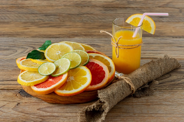 Glasses of juice and citrus fruits on a wooden table. rustic style.