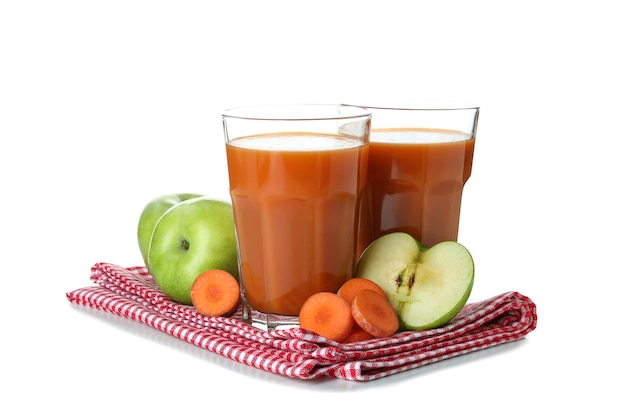 Glasses of juice and ingredients on towel isolated on white