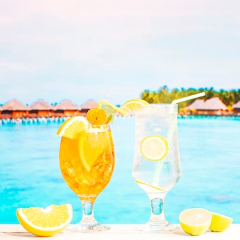 Glasses of juicy lemon orange drinks with straw and sliced citruses
