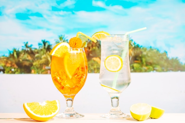 Glasses of juicy orange lemon drinks with straw and sliced citruses