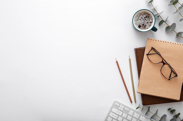 안경 키보드 커피 컵 노트북 사무용품은 책상 위에 있습니다. 흰색 바탕에 복사 공간이 있는 현대적인 책상 작업 공간.