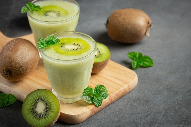 Glasses of kiwi juice put on wooden cutting board