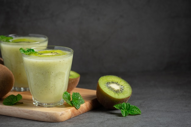 Bicchieri di succo di kiwi messi sul tagliere di legno