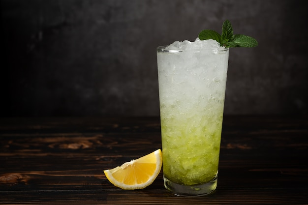 Glasses of lemon soda with ice and fresh mint on wooden table.