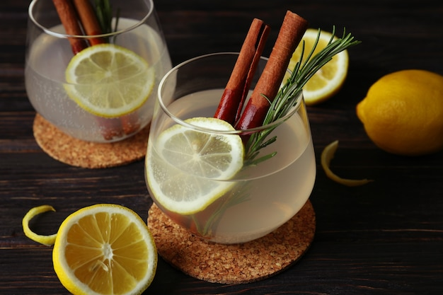 Glasses of lemonade on wooden, close up