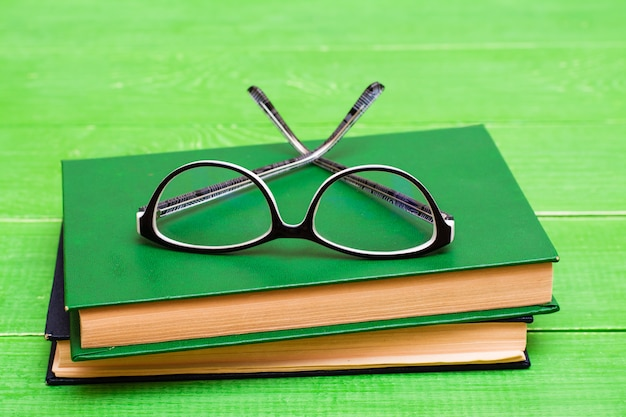 Glasses lie on two hardcover books on a green wooden table