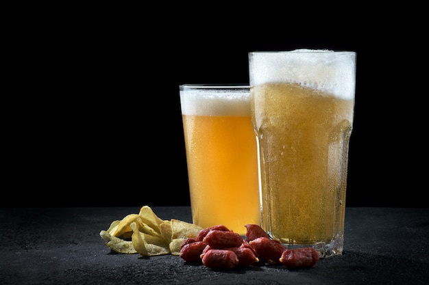 Glasses of light and wheat beer with chips and sausages on a dark background