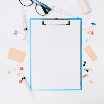 Glasses and medications around clipboard