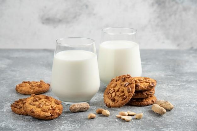 Bicchieri di latte e biscotti fatti in casa con arachidi organiche sul tavolo di marmo.