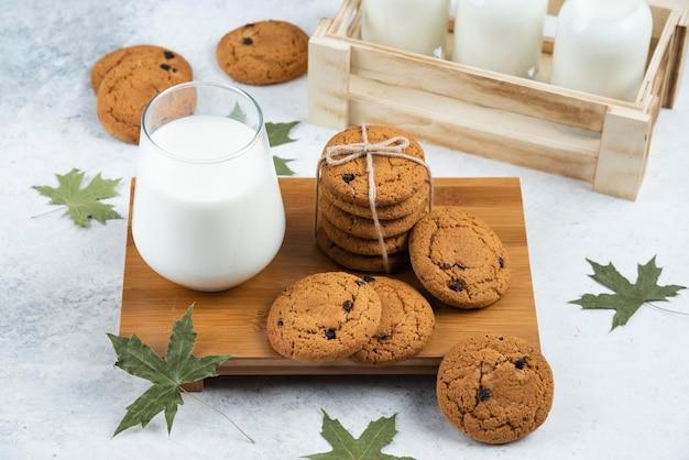 Bicchieri di latte con biscotti al cioccolato e foglie.