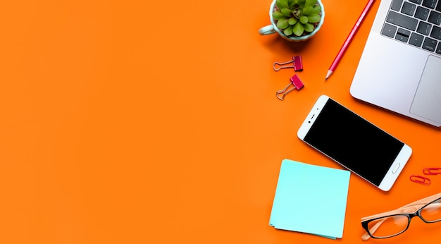 Glasses, mobile phone, laptop, flower, stickers, paper clips, stationery on an orange background. workplace freelancer, businessman, entrepreneur.