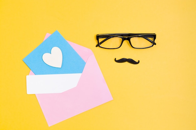 Glasses, mustache, pink envelope, wooden heart and a card on a yellow background, father's day concept